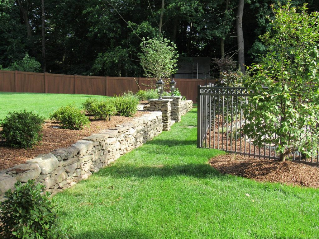 primo landscape design rock wall and green grass
